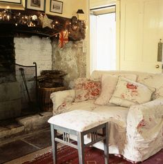 English country cottage sitting room with inglenook fireplace and pretty slip covered sofa