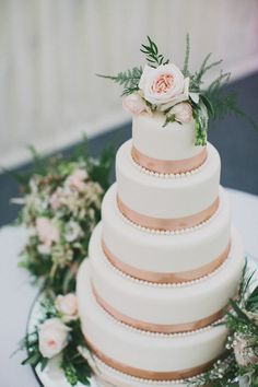 Wedding packed with shades of pink, champagne, roses. Gorgeous 5 tiered cake!