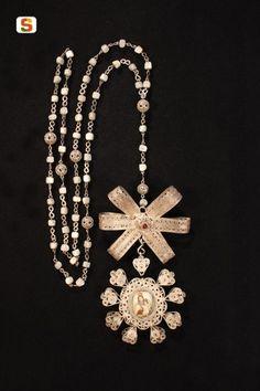 Rosario in filigrana d'argento con medaglione portareliquie e motivo decorativo tipico a fiocco.