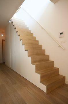 Onder deze trap creëerden we een kast op maat, zo gaat de plaats onder de trap niet verloren en oogt het geheel strak. Intussen geeft de parket en de trap het interieur een warme uitstraling. Kast-ID Antwerpen