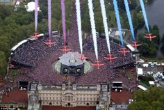 Awesome sight: The Red Arrows soar over Buckingham palace and the crowds gathered along the Mall