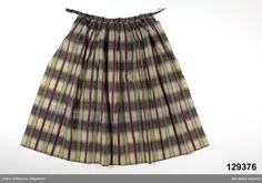 Blekinge 1840-1860 | Förkläde av tunn yllemuslin storrutigt i brunt och ljusgrått med ripsvävda ränder i starkt rödlila silke och smalare i grönt silke, även smala ripsränder i brunt och vitt bomullsgarn. Lagda veck i midjan mot 3 cm bred linning av samma tyg. Knytband borttagna, mellanblå silketrådar visar att de varit av blått siden. Tyget sannolikt importerat.