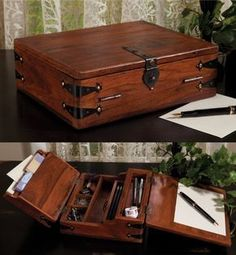 Wooden antique reproduction writing storage box with writing surface, divided compartments and distressed details to store writing implements, craft notions or painting supplies on a desk or for display in a living room or den.