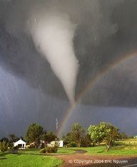 The scene might have been considered serene if it werent for the tornado. During 2004 in Kansas, storm chaser Eric Nguyen photographed this budding twister in a different light -- the light of a rainbow. Pictured above, a white tornado cloud descends from a dark storm cloud. The Sun, peeking through a clear patch of sky to the left, illuminates some buildings in the foreground. Sunlight refle