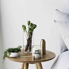 good morning candle from zakkia on round blonde timber side table beside pale bed linen