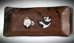 Brown stoneware sushi/tapas tray with panda family, including baby! Bamboo represents longevity and pandas represent balance and perfection. Textured Chinese red exterior.