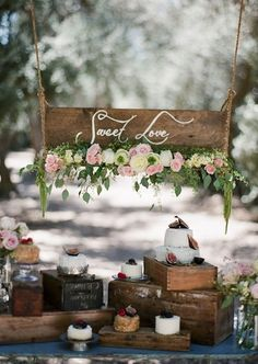 Rustic outdoor display with flowers and wooden boxes #wedding #weddingcupcakes…