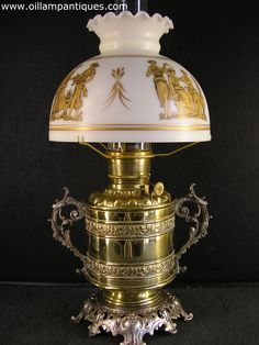 The embossed bands and ornate handles on the cylindrical brass vase of this antique kerosene lamp (circa 1893) set it apart from most others. The vintage gold decorated shade reflects its classical style and compliments it perfectly.