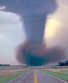 Storms Tornadoes:  A tornado thunders down a lone highway, churning up earth.