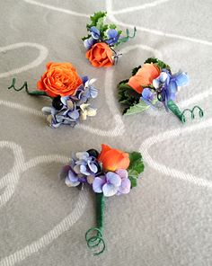 blue and orange theme boutonniere...with orange rose, pepper and blue hydrangea...from http://doingso.com/