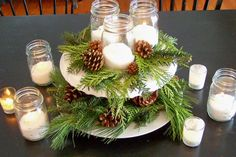 Simple yet very effect festive table centrepiece. Cake stand adorned with firs and cones accompanied by candles in jars.