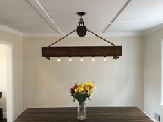 This rustic cedar beam with Edison bulbs is suspended by an authentic antique barn pulley and 3/4 inch rope. The 6x6 beam is hand planed and