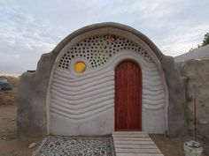 Art and function meet in this beautiful vault house built by Apprentices at Cal-Earth. The glass art is made completely of recycled bottles and shines colorful light inside and out!