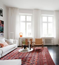 This is the sort of feel I am going for in the living room. Light and white, gorgeous rug, white curtains.
