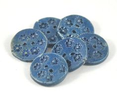 Give your handmade gloves, scarf or cardigan a unique flair with this set of six small round rustic handmade ceramic buttons featuring a stamped daisy flower design highlighted by a blue tonal glaze. Each button has two holes for sewing to garments. Buttons come packaged threaded on embroidery cotton. Other glaze finished are available... simply contact me to discuss options.  Product specification: Fired to 1300C (2372 F) - stoneware, making the buttons durable and scratch-proof. 1.8cm…