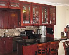 Glass door kitchen cabinets in combination with granite countertops and mosaic tile backsplash