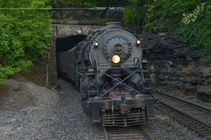 Norfolk and Western Y6a #2156 shows some articulation as it leans into the curve exiting the east portal of Welch Tunnel in Welch, West Virginia.  Norfolk Southern train 956 completed the repositioning move this afternoon, having towed 2156 at no more than 25 mph from St Louis to Roanoke in a little over 3 and a half days.  Special thanks go to all of the mechanical and operating crews, supervisors, yard personnel, and dispatchers involved, especially Senior General Foreman of Steam Bob…