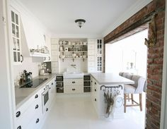 White kitchen, Brick wall, studded fabric chairs, white backsplash