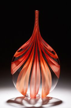 Red & Orange Cane Bottle by Chris McCarthy. Vibrant ribbons of *caneworked:cane* glass shift from red to orange, opaque to translucent as they billow over this sophisticated, flattened *blown glass* vessel.