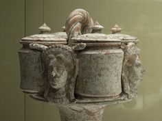 """Kernos resting on a pedestal and holding four small vessels. Vase coming from Canosa, Puglia. A braided handle and four female heads showing richly decorated hairstyles embellish the kermos. Two snakes near the heads suggest to identify the heads as portraits of the goddess Kore [?].  """"The kernos was used primarily in the cults of Demeter and Kore, and of Cybele and Attis.""""    Clay painted kernos Apula (Canosa) pottery 3rd cent. BC From Orvieto Florence, Museo Archeologico Etrusco"""