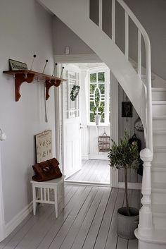 Licht grijze muren in combinatie met witte trap en kozijnen.