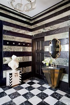 In the pavilion bath of this Kelly Wearstler–designed Bel Air, California, home, striped walls play off the checkerboard floor, while an oval 1920s French mirror is paired with an angular brass vanity | archdigest.com