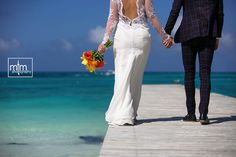 Walking down the pier.  RIU Cancun Wedding Photography. Unique Mexico Beach Wedding Ideas. Newlywed photographer. Elope & Honeymoon in Mexico. Best Destination Wedding Photographer. Riviera Maya Wedding Planner.