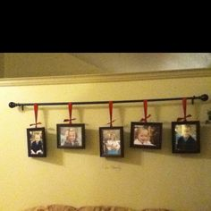 A curtain rod with family pictures hanging from it.