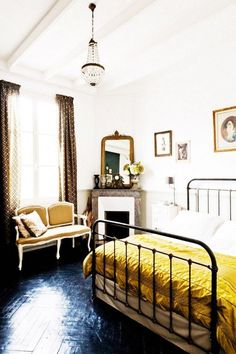 Rustic inspired bedroom with a vintage metal headboard, a yellow throw blanket…