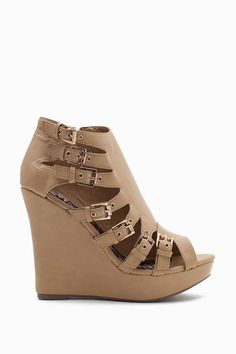 Buckle up! A pair of edgy leatherette wedges featuring side cutouts with buckled detailing. Open toe. Side zip closure. Textured outsole.