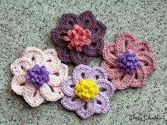 Broszki z szydełkowymi kwiatami w kolorach różu i fioletu.  Brooch with crochet flowers in pink and purple.
