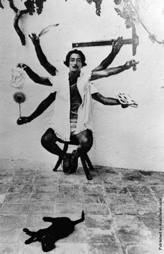 """Dali resembles the Hindu goddess of death and destruction in a multiple exposure pose at his home in Cadaques in 1955. """"Surrealism is destructive, but it destroys only what it considers to be shackles limiting our vision,"""" he said."""