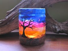 Sunset Jar Candle - Salsa jar covered with tissue and mulberry papers. Tree was painted on with black dimensional fabric paint.