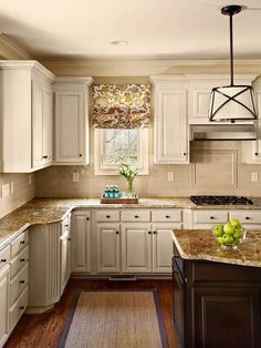 This traditional kitchen features painted cabinets, dark brown granite and statement lighting. I would definitely do more colorful fabric, but love the roman shades. Perfect.