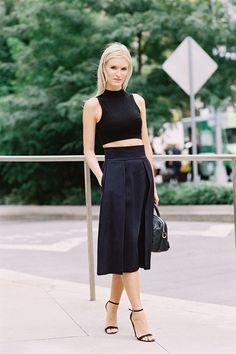 Black crop top, black pleated midi skirt, and black ankle strap heels