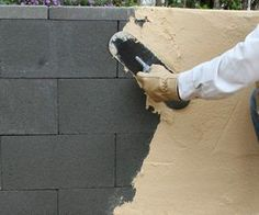 Applying surface-bonding cement to a dry stacked concrete block wall