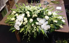 White and green casket spray including orchids. #sympathyflowers #floraltribute. F26
