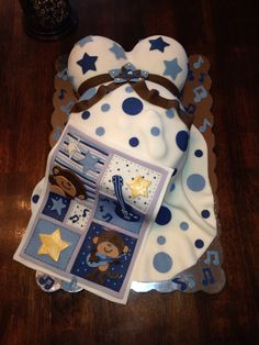 Baby shower belly cake with rock and roll monkey blanket replica draped across belly. Decorated with stars and music notes