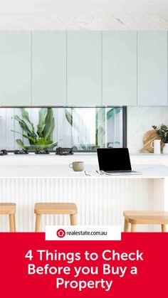 Minimal blue and white kitchen with glass splashback looking out to greenery in garden. White benchtops with timber stools.
