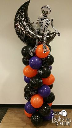Halloween Balloon Column in black, orange and purple. With a black moon and skeleton mylar balloon on top.