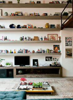 Televisão, enfeites e livros se organizam nas prateleiras e no rack de argamassa armada moldados na obra. O conjunto inclui uma lareira a gás sem coifa. Tapete da Phenicia Concept.
