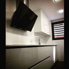 Muebles de cocina lacados blanco brillo Apertura Gola lacada en negro Encimera Silestone blanco Zeus Campana Pando cristal negro
