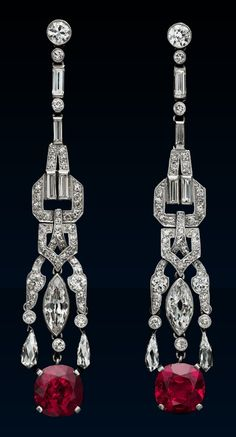A pair of Art Deco diamond and ruby earrings, probably French, circa 1920. Each designed as a chain of alternate brilliant and baguette-cut diamonds linked to a diamond-set buckle and strap motif terminating in a marquise diamond collet and a cushion-shaped ruby flanked by a briolette hanging from diamond-set tassels, mounted in platinum. Length 6.1cm.