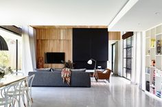 The large fireplace in the main living room is clad in black sheet metal and punctuates the timber walls and ceilings. Wolseley House by McKimm Living Room Interior, Living Room Furniture, Living Area, Living Spaces, Living Rooms, Casual Family Rooms, Timber Walls, Australian Interior Design, Terrazzo Flooring