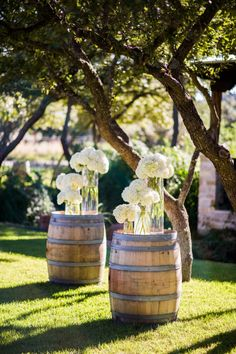 Rustic meets chic. Wine barrels paired with long glass stem flower arrangements. Yes!