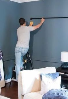 Hang pics from a curtain rod He screws a 10 ft. pipe in the living room wall for one GENIUS reason