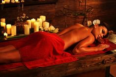Young woman lying on wooden spa bed. Massage in spa salon. Girl on candles background in massage spa salon.