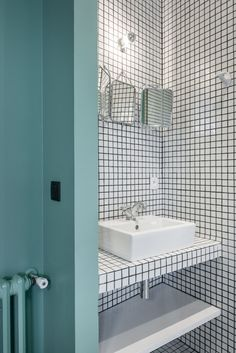 Black and white tile bathroom with turquoise wall