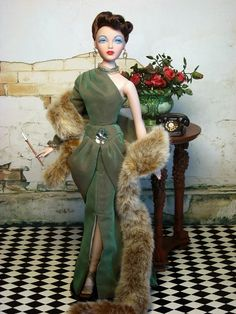 Cold Shoulder Miss Marshall is stunning in the sage green, asymmetric gown designed originally for Madra Lord by Jose Ferrand, circa 1942. The Grecian-styled design was inspired by the illustrations of Salvador Dali, Christian Berard, and Marcel Vertes in the 1930's and 40's. OOAK cigarette holder is from Mystyna. Encore Gene Marshall is from Ashton Drake.
