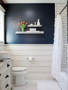 Chip and Joanna reconfigured and opened up the bathroom, stealing space from an adjacent linen closet. They also gave it a whole new look with painted shiplap, white subway tile and rich navy wall paint.